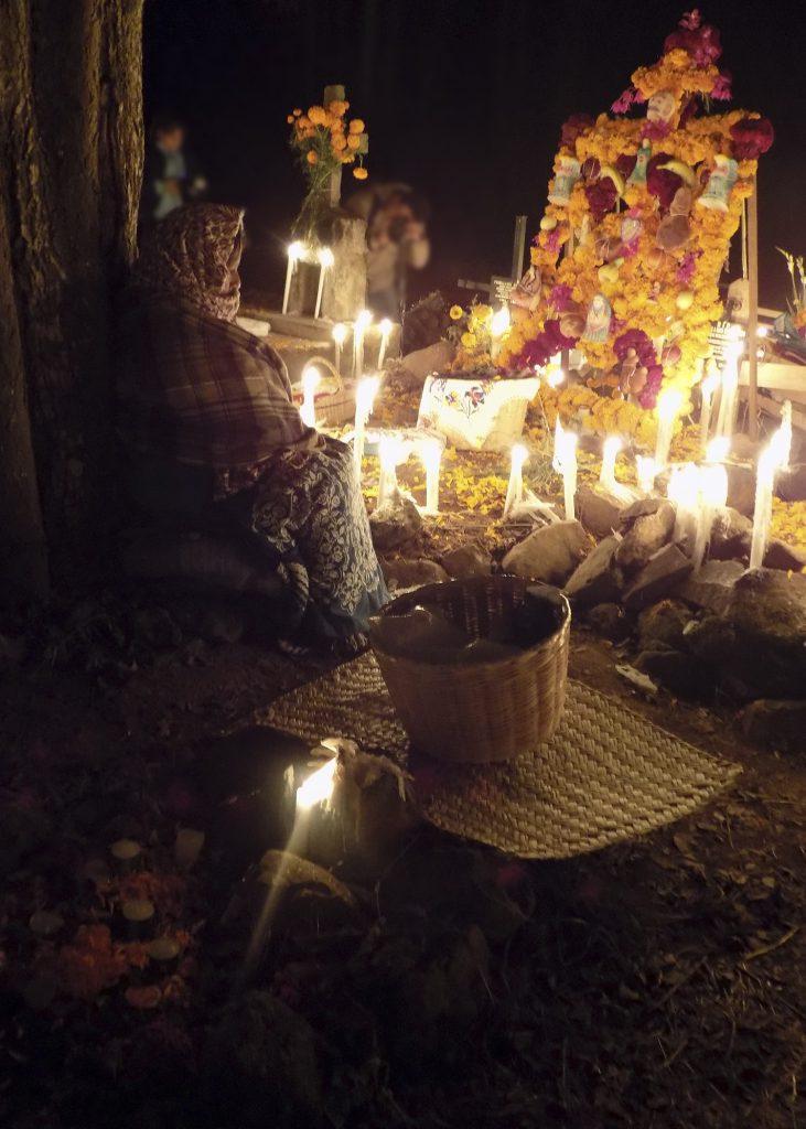Une femme se tient assise devant un autel, de soir, des chandelles éclairent la scène.