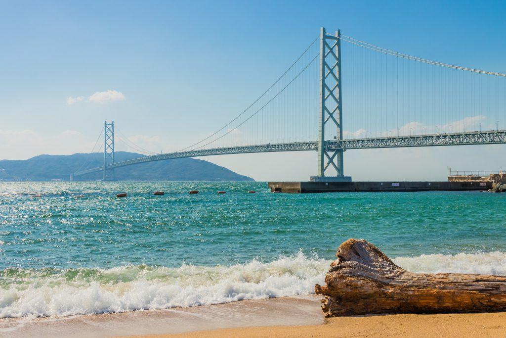 Une image de la berge de Kobe avec, au loin, un pont et des montagnes.