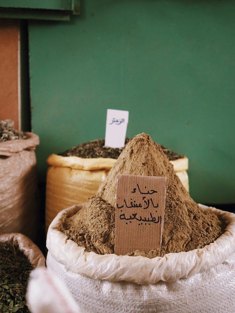 Des sacs d'épices et d'herbes dans les lesquels sont plantés des cartons avec de l'écriture arabe.