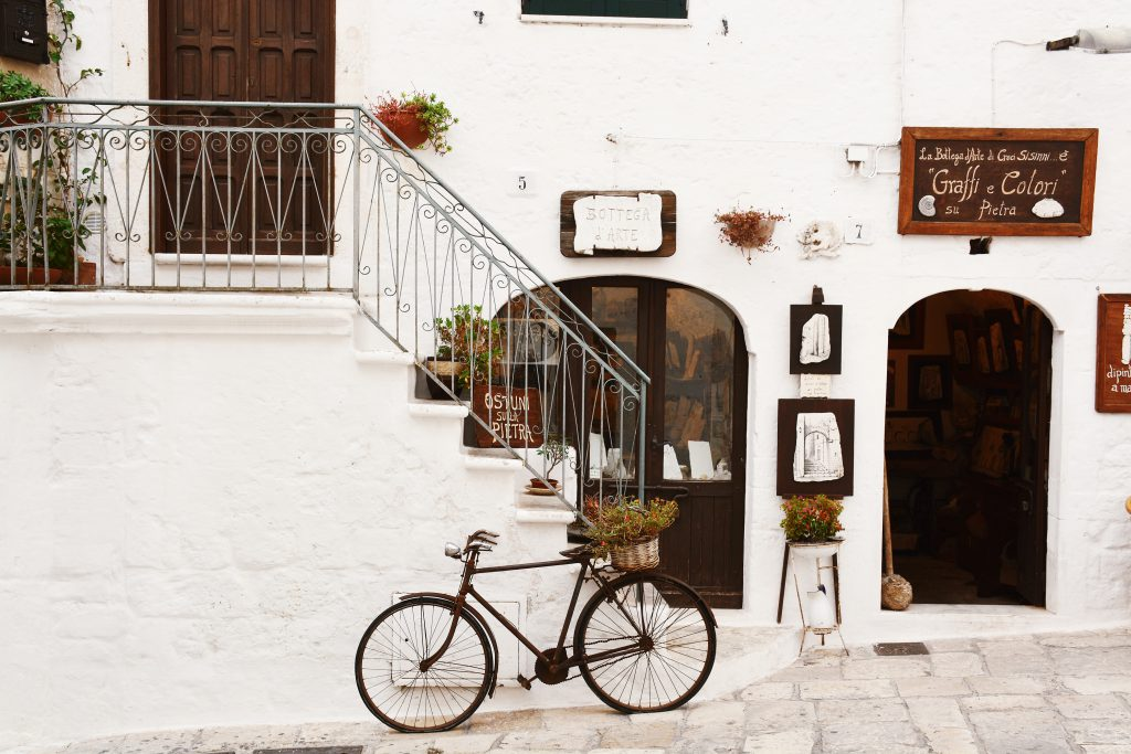 A bike with a flower basket in front of a café in Italy.