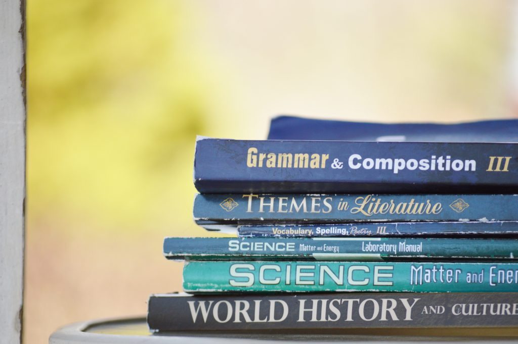Books on a table: Grammar & Composition III; Themes in Literature; Vocabulary, Spelling, Poetry III; etc.