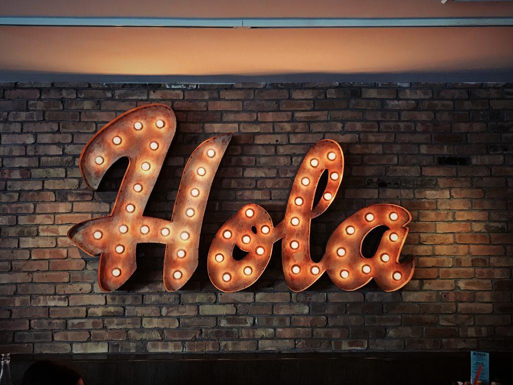 """""""Hola"""" écrit en lettres lumineuses sur un mur de briques."""
