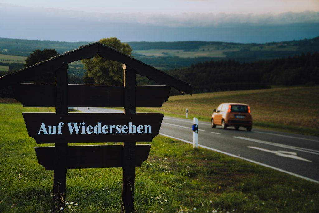"""Une pancarte au bord d'une route indique """"Auf Weidersehen""""."""