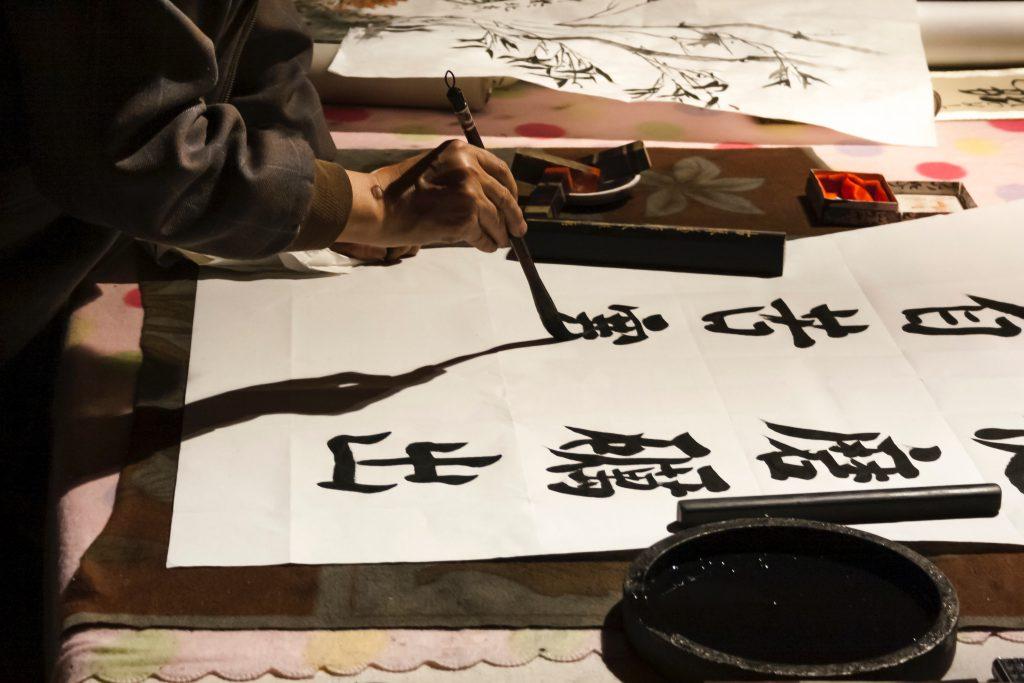 Une personne fait de la calligraphie Kanji.