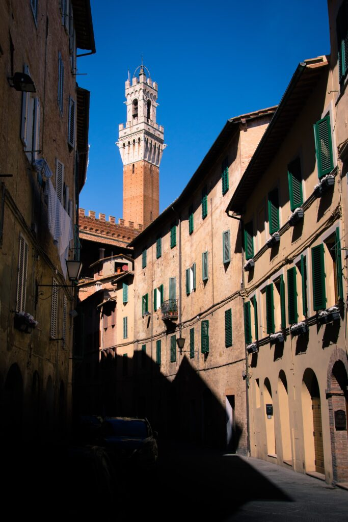 Image d'une petite rue dans Sienne, un côté complètement ensoleillé; l'autre complètement dans l'ombre.