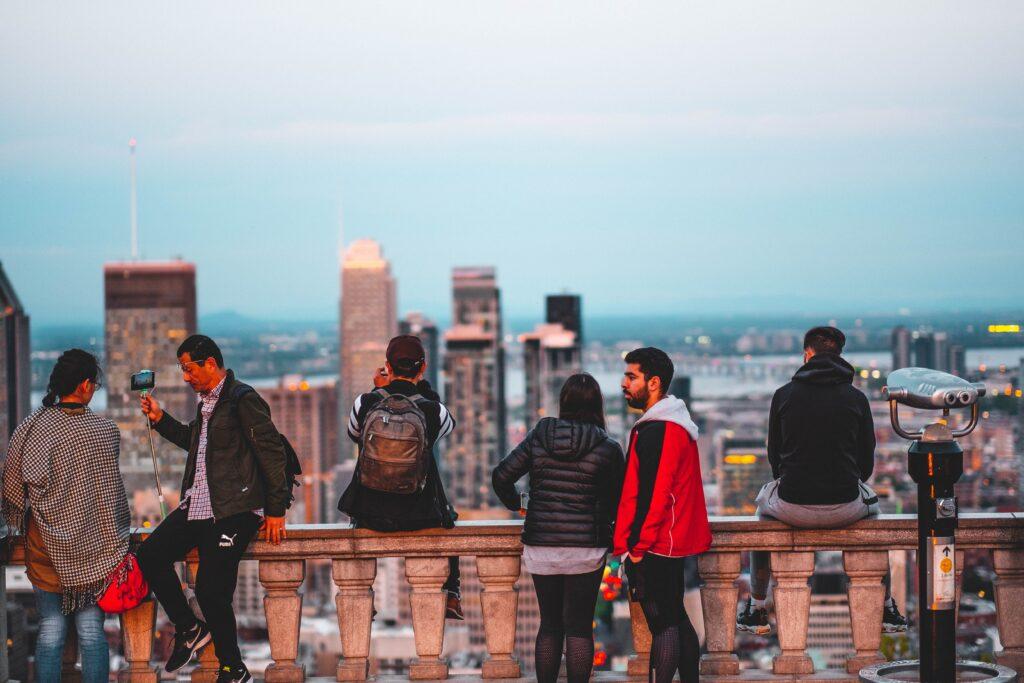 Vue de Montréal à partir du mont Royal. En avant-plan, des gens observe la vue. Montreal's skyline as viewed from mount Royal. At the front of the picture, people are taking in the view.